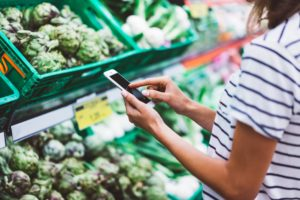 woman scanning produce with phone at grocery store